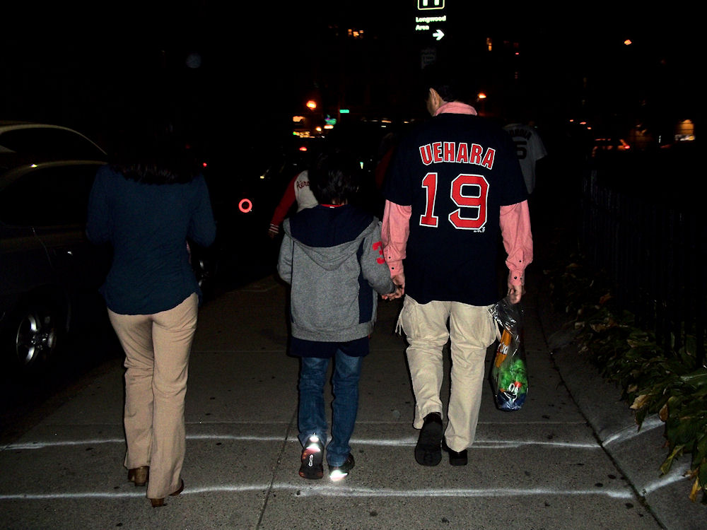 An Asian/Asian American father with (presumably) his wife and son, walking home from Fenway Park.