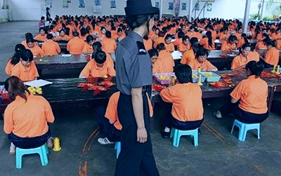 Inmates in a Chinese labor camp work under watch of a guard.