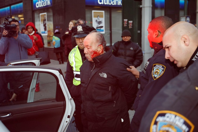 His head bloody, 84 year old Kang Wong is escorted into a police car before being charged with jaywalking. Photo credit: G.N. Miller / NY Post.