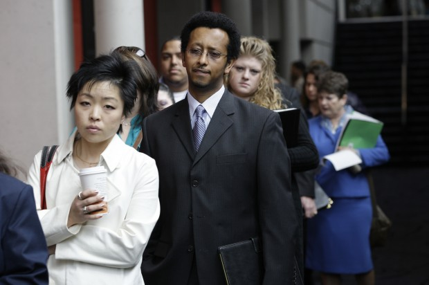 Job seekers wait in line at a job fair in Seattle.  (AP/Photo Credit Ted Warren).