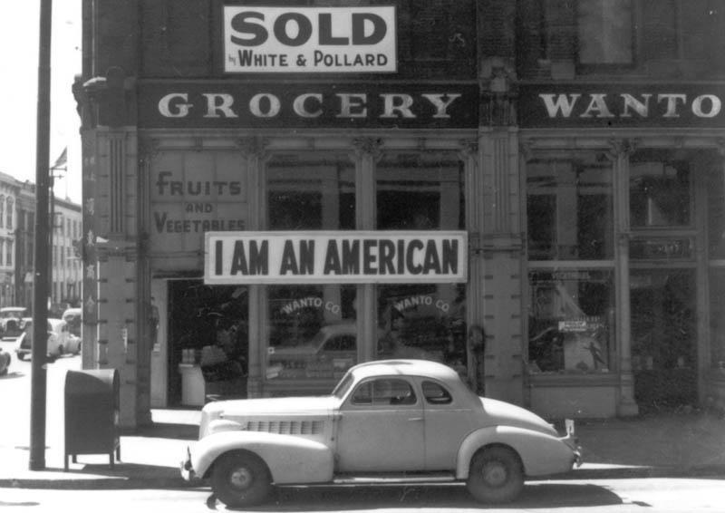 A sign erected in 1942 on a store owned by a Japanese American, uging his neighbours to see past the hate. Later, the owner was interned and the store sold by the government to profit local (non-Japanese) business owners and residents. (source: AP/Dorothea Lange)