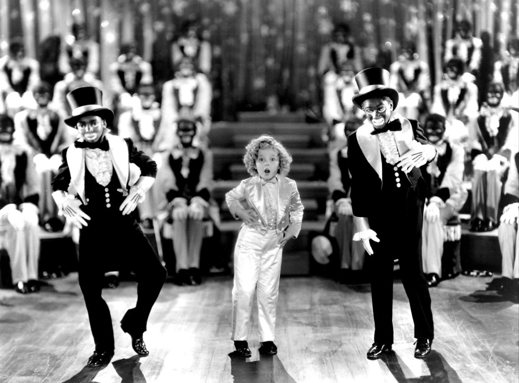 Shirley Temple dances with two men in Blackface, while other actors also in Blackface look on, from Dimples (1936).