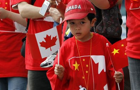 A boy holds up Chinese and Canadian flags (photo credit: Vancouver Sun)