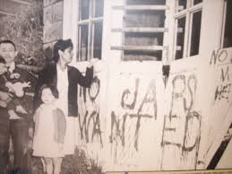 A family stands next a spray painted message.