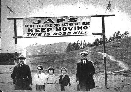 A family stands below a sign explaining the attitudes of Rose Hill.