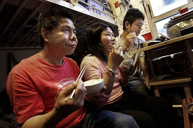 Ba Qi Mo's son and his family eat an evening meal while watching TV in their SRO. The bottom bunk of their bunk bed is used as living space, since there is no room for chairs. (Photo credit: Brant Ward, The Chronicle)