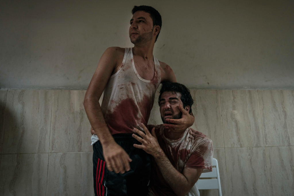 Two brothers grieve the death of their father at Nasser hospital, following an Israeli airstrike that destroyed the family home. (Photo credit: Sergey Ponomarev / The New York Times)