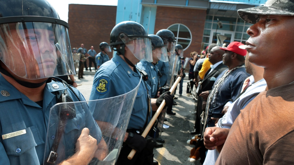 """Riot police are dispatched to Ferguson, to """"protect"""" residents from a peaceful congregation of Black protesters."""