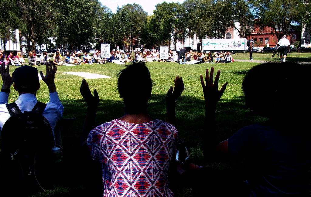 Students engaging in an approximately 15-minute moment of silence with hands raised, on the New Haven Green. (Photo credit: Reappropriate)