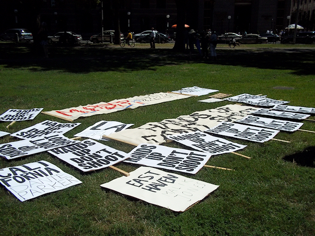 Signs on the ground, marking the site of the protest. (Photo credit: Reappropriate)