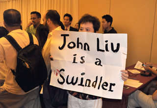 "A protester at a recent State Senate candidate's forum holds up a sign expressing his views on State Senate candidate John Liu. Other protesters unfurled a large sign demanding that Liu be arrested ""to prevent further harm to the U.S.""."