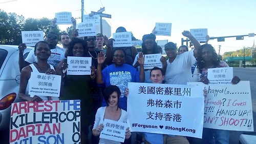Ferguson protesters hold up signs in solidarity with the Hong Kong protests.