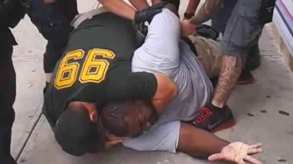 Image of NYPD wrestling with Garner and placing him in a chokehold, moments before his death.