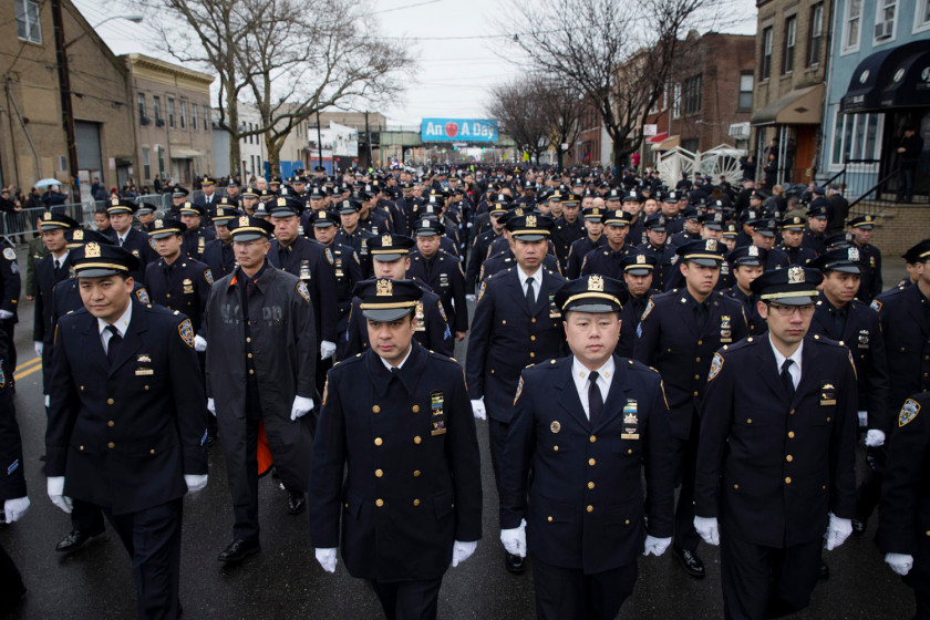 Police officers arrive to the funeral of New York Police Department Officer Wenjian Liu at Aievoli Funeral Home, Sunday, Jan. 4, 2015, in the Brooklyn borough of New York. (Photo credit: AP Photo/John Minchillo)
