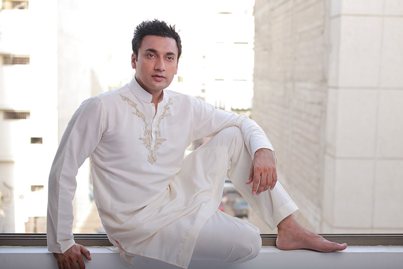 A man models a white shalmar kameez with the intricate embroidery style popular in Pakistan.