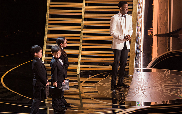 Chris Rock introduces three young Asian/Asian American children at Oscars 2016. (Photo credit: Rex)