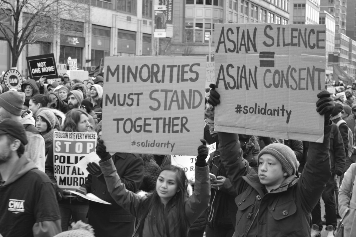 Asian Americans hold signs at a protest. (Photo credit: Flickr / Marcela McGreal)