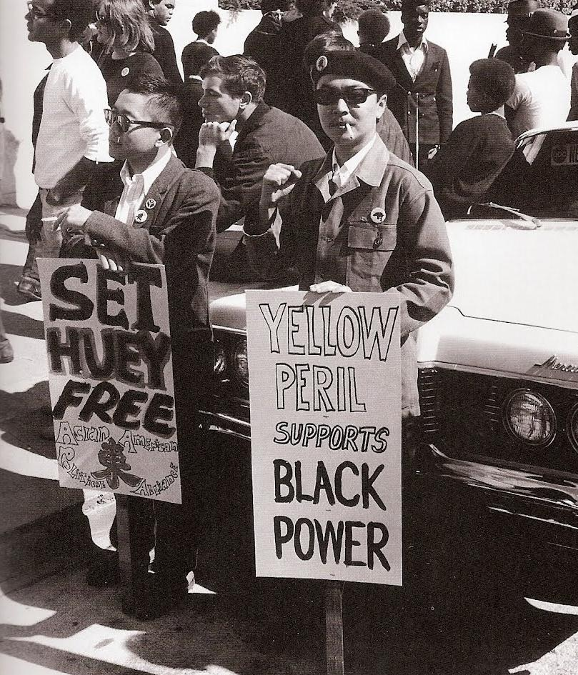 "Richard Aoki, in a now famous image, holds a sign reading""Yellow Peril Support Black Power."" (Photo Credit: Unknown)"